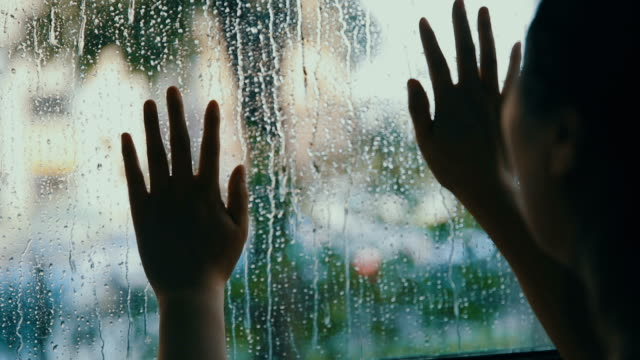 Woman hand touch window with rain drops