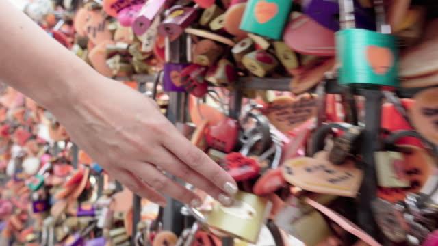 woman hand touching a locks hanging wall video