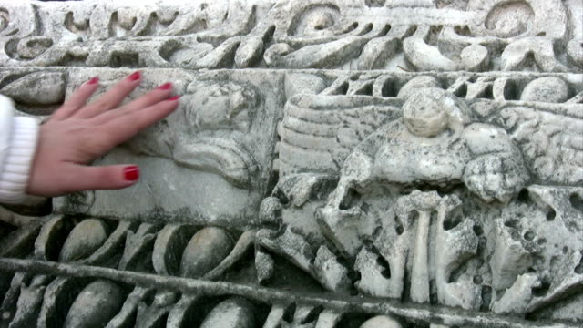 Woman hand touching ancient stone video