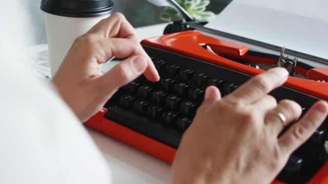 Woman hand typing on red vintage typewriter