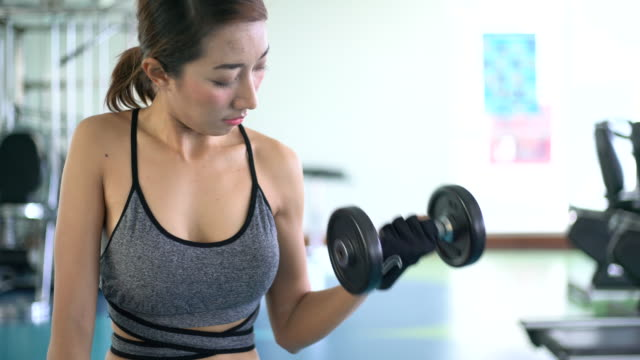 Woman hand weight with a dumbbell in health club video