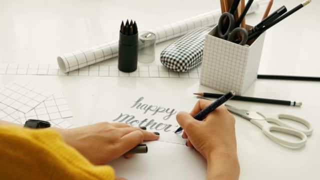 母の日の概念を提示する白いテーブルで「母の日」の文言を描きながら女を手します。 - 母の日点の映像素材/bロール