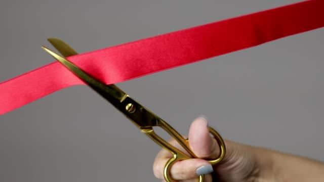 kırmızı şerit kesme altın makas ile bir kadın el - ribbon stok videoları ve detay görüntü çekimi