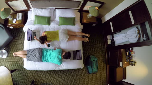 TOP DOWN Woman hands a cell phone to her boyfriend while working from hotel room