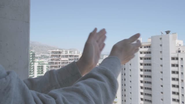 woman hands applauding medical staff from their balcony. people in spain clapping gratitude on balconies and windows in support of health workers, doctors and nurses during the coronavirus pandemic - battere le mani esprimere a gesti video stock e b–roll