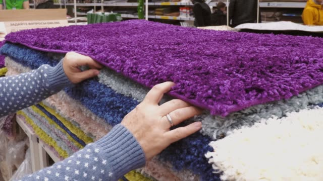 woman hands choosing a textile carpets in a hardware store in diy shopping mall - moquette video stock e b–roll
