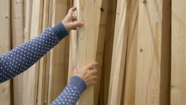 vídeos y material grabado en eventos de stock de manos de mujer eligiendo un tablones de madera en una ferretería en el centro comercial diy - material de construcción