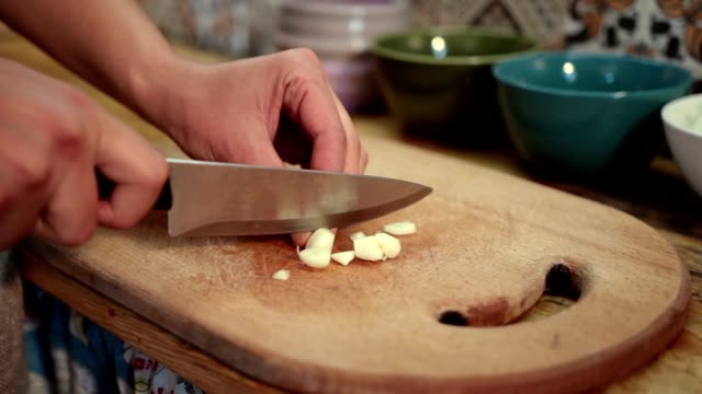 Woman hands chopping fresh garlic with knife