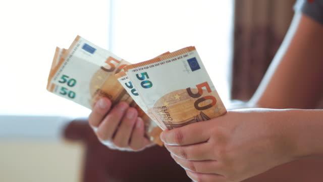 kvinnan händer räkna euro sedlar pengar och kalkylator kostnad. - lön bildbanksvideor och videomaterial från bakom kulisserna