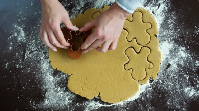 woman hands cut gingerbread man cookies from raw dough using cutter top view woman hands cut gingerbread man cookies from raw rolled dough using cookie cutter top view. Christmas preparation, homemade food, festive mood gingerbread man stock videos & royalty-free footage