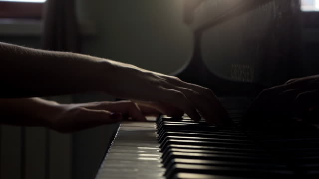 Woman hands finish plays on piano and close lid of piano close-up in slow motion