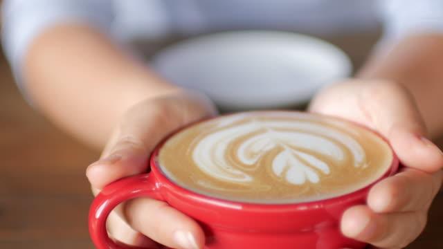 frau die hände hält eine tasse kaffee im café kaffee - barista stock-videos und b-roll-filmmaterial