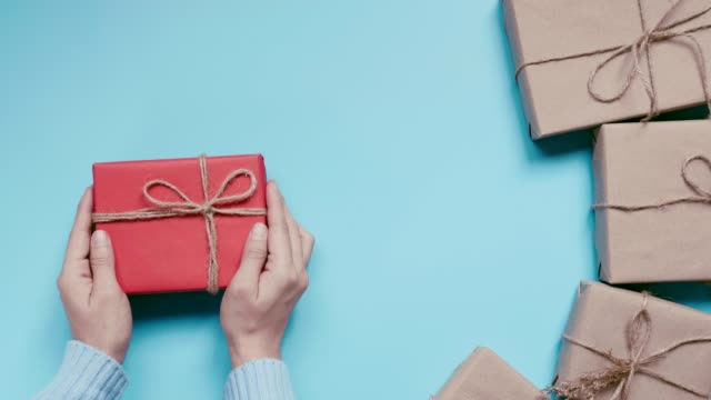 Woman Hands holding craft paper gift box on blue background. for present Christmas, new year, valentine day or anniversary.