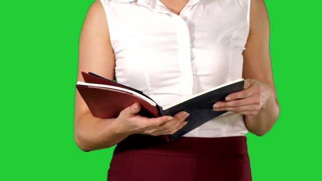 stockvideo's en b-roll-footage met vrouw handen houden notebook en het draaien van pagina's op een groen scherm, chromakey, key te kijken - magazine mockup