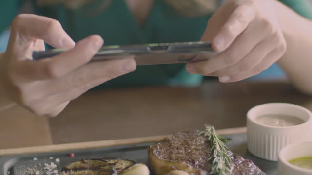 Woman hands make a food photo of steak using phone The food photo concept: female hands holding smartphone and making a picture of restaurant dish on the wooden plate. Delicious meat steak with grilled vegetables, sauces, grains of salt and herbs passion stock videos & royalty-free footage