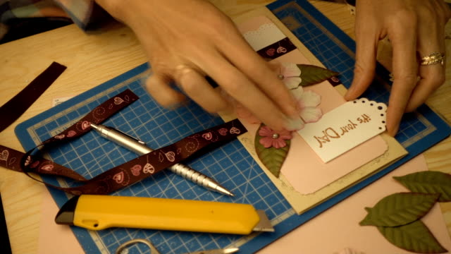 woman hands making a scrapbooking holiday gift postcard video
