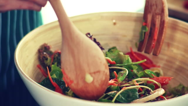 vídeos y material grabado en eventos de stock de manos de mujer mezclando verduras en ensaladera. - comida tailandesa
