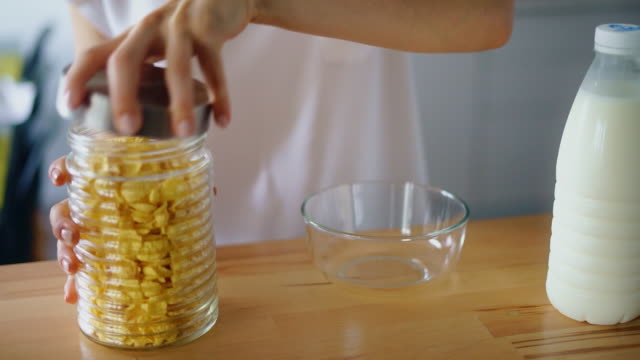 Woman hands opening jar and pouring corn flakes into glass bowl Woman hands opening jar and pouring corn flakes into glass bowl. Close up preparing cereals breakfast with milk on kitchen table. Traditional breakfast in morning at home. Breakfast time concept jar stock videos & royalty-free footage