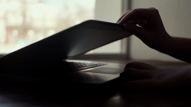 Woman hands opens the lid of a laptop close-up near the window in slow motion