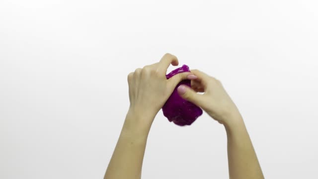 Woman hands playing oddly satisfying purple slime. White background. Antistress