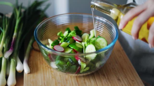 女性が新鮮な春サラダとガラスのボウルにオリーブ油を注ぐを手します。 - サラダ点の映像素材/bロール