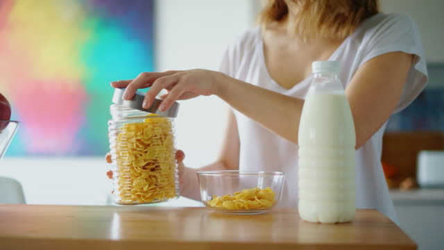 vídeos de stock e filmes b-roll de woman hands preparing cereals with milk on kitchen table - granola