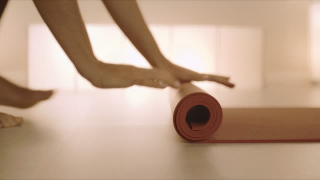woman hands rolling up yoga mat after training.girl folding fitness mat on floor - materassino ginnico video stock e b–roll