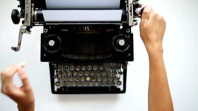 Woman hands set up paper into typewriter High angle view of secretary prints on vintage typing machine. typewriter stock videos & royalty-free footage