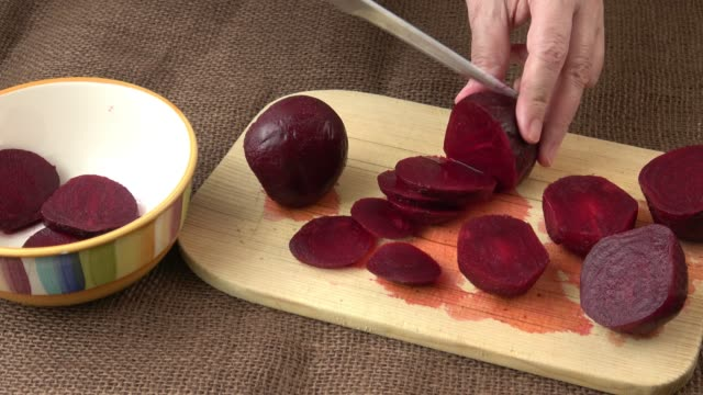 Woman hands slicing beetroot on wooden cutting board. Home cooking concept. Salad or any vegetarian dish.