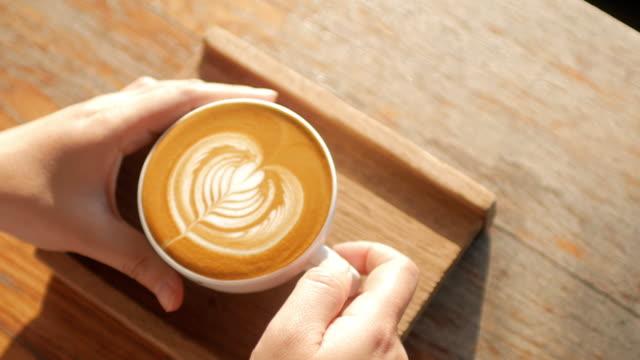 frau hände nehmen sie einen kaffee auf holztisch im kaffee café - milchkaffee stock-videos und b-roll-filmmaterial