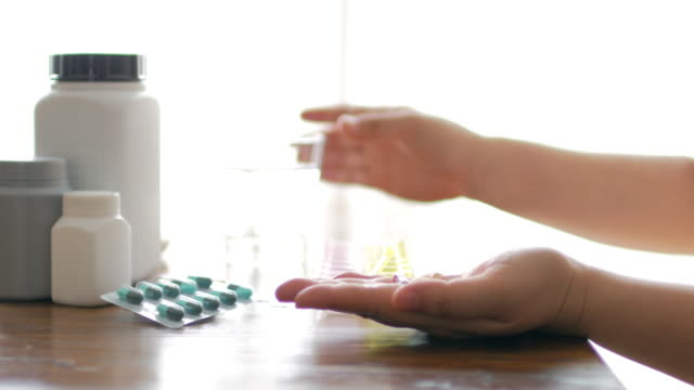 woman hands take a medicine with drinking water , dolly shot - antibiotico video stock e b–roll