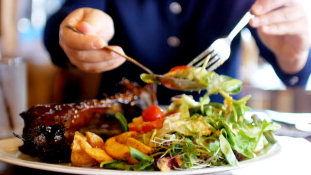 Woman hands take a salad ready for eating on dish with steak video