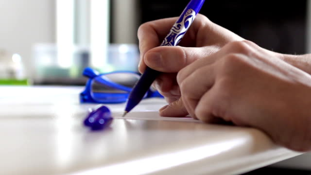 Woman hands taking a blue pen and writing on a post it in a office video