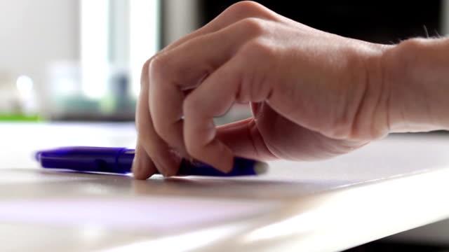 Woman hands taking a blue pen on a white desktop in a office video