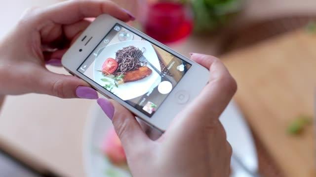 vídeos de stock, filmes e b-roll de mãos de mulher tirando fotos de jantar comida pelo smartphone - gourmet