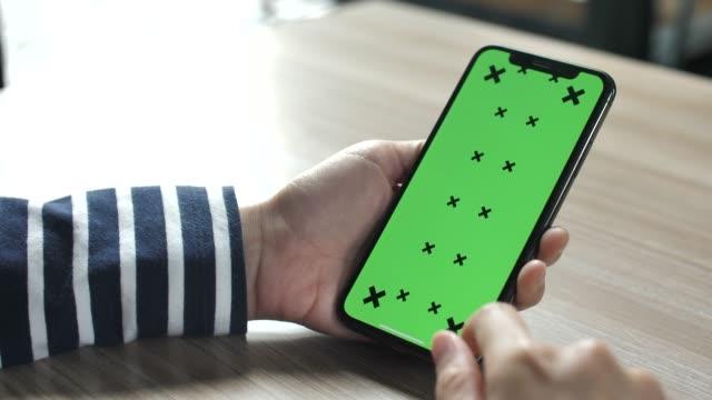 frau hände berühren smartphone mit grünem bildschirm - schlüssel videos stock-videos und b-roll-filmmaterial