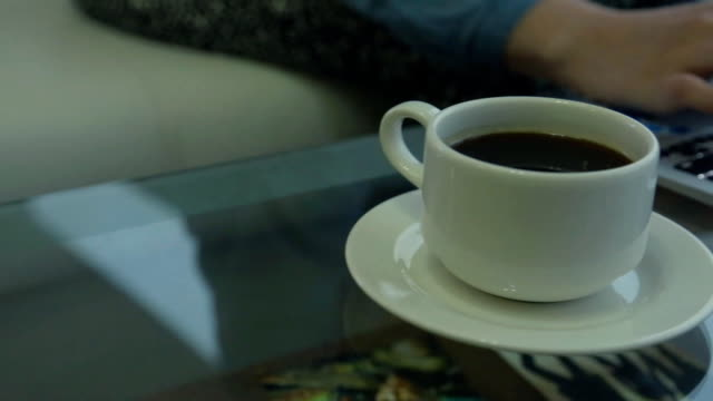 Woman hands typing on a ring with a modern laptop on a glass table with a cup of coffee video