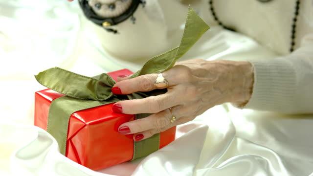 woman hands untied bow on gift box. - nastro per capelli video stock e b–roll