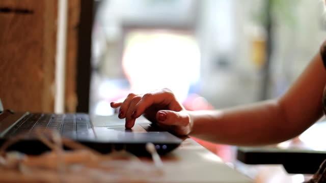 Mains de femme en utilisant l'ordinateur portable dans le café du matin - Vidéo