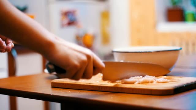家庭の台所で木製のまな板で肉を切るナイフで女の手。スローモーション - ローフード点の映像素材/bロール