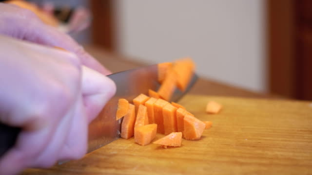 woman hands with a knife sliced carrot with knife on a wooden kitchen board in a home kitchen - abbigliamento formale video stock e b–roll