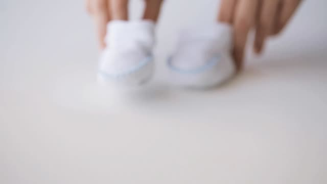woman hands with baby booties at home motherhood, people, clothing and expectation concept - woman hands with baby booties walking on table at home baby booties stock videos & royalty-free footage