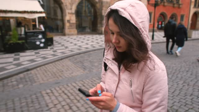 Woman hands with blue manicure prints text message with fingers street in city.