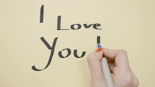 Woman hands writing I love you message for her boyfriend on a piece of paper using black pen and drawing a heart video