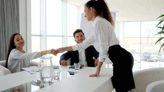 woman handshake in modern office on interview, conversation on job with secretary and boss in boardroom, female candidate woman handshake in modern office on interview, conversation on job with secretary and boss in boardroom, female candidate during job interview into large company at white and spacious office arthropod stock videos & royalty-free footage