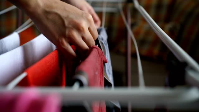 stockvideo's en b-roll-footage met vrouw opknoping kleren - hangen
