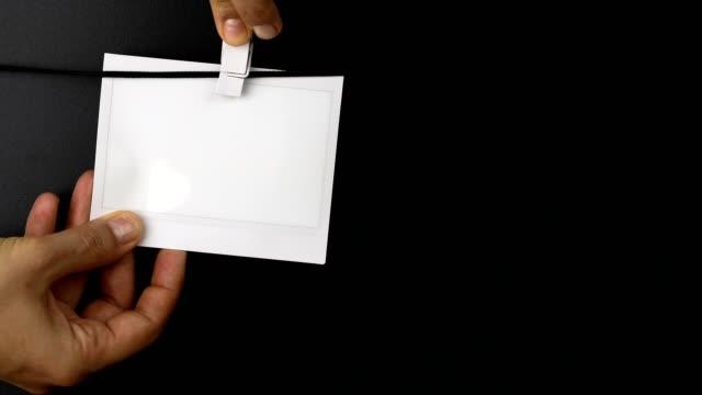 vídeos de stock, filmes e b-roll de mulher pendurando quadro de fotos instantâneas em uma corda - polaroid