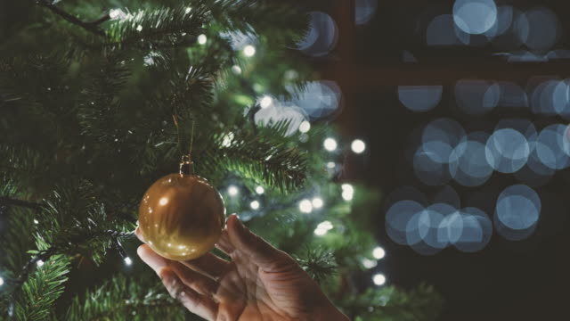 CU Woman hanging ornament on Christmas tree with lights Woman hanging ornament on Christmas tree with lights. LR pan,Rack Focus,Real Time. hanging stock videos & royalty-free footage