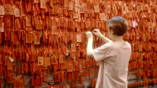 Woman hanging prayer offerings for good luck