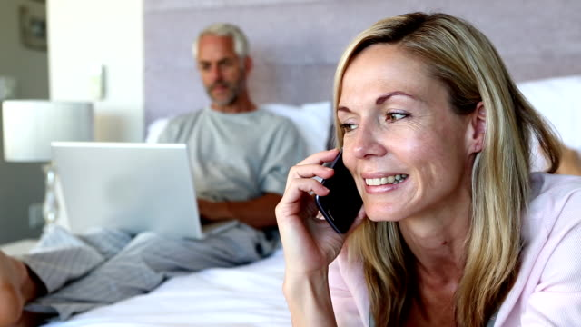 Woman hanging up the phone and talking to her husband video